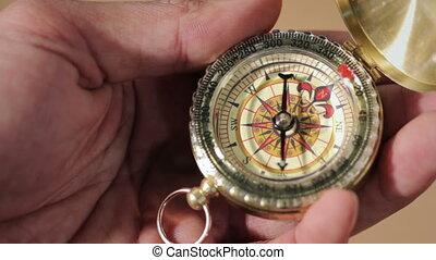 Compass, a navigational instrument - Hand holding a compass...