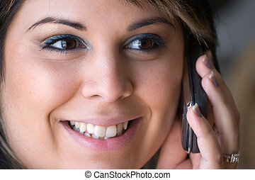 Cell Phone Conversation - A beautiful young woman talking on...