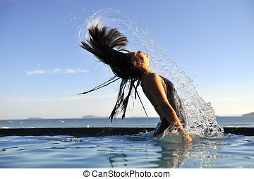 Refreshing - Beautiful swimsuit model splashing water on...