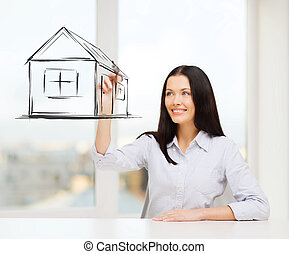 smiling woman drawing house on virtual screen - real estate,...