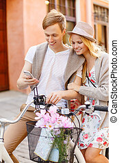 couple with smartphone and bicycles in the city - summer...