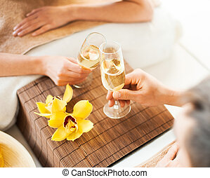 woman and man hands with champagne glasses - spa, health,...