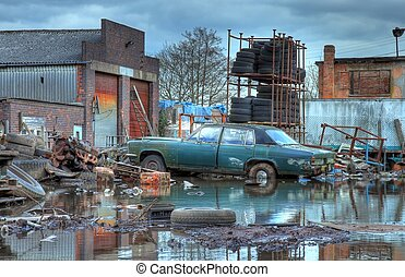 Scrapyard, England - Scrapyard showing flood water and old...
