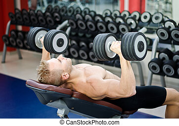 Muscular young man shirtless, training pecs on gym bench -...