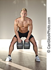 Muscular young man shirtless in gym training with kettlebells