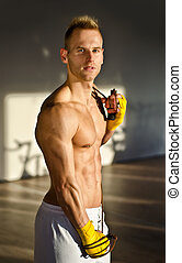 Shirtless muscular young man standing with jumping rope in gym