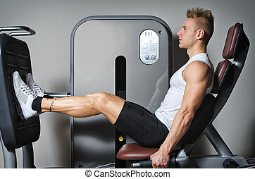 Attractive and fit young man in gym working out legs