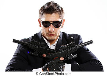 Men in black suit holding gun - Young man in black suit...
