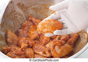 Hand holding raw chicken wings