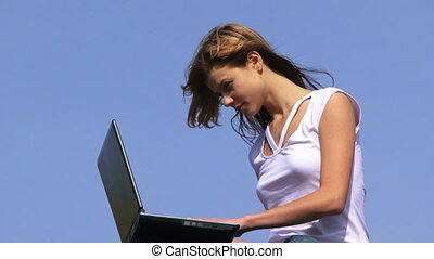 Using laptop - Teenage girl using laptop outdoors