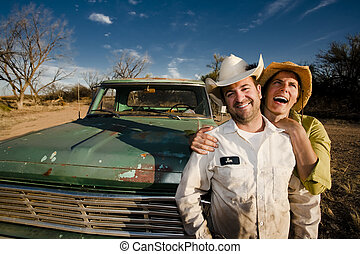 Couple with a Pickup Truck - Man and woman in cowboy hats...