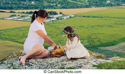 Picnic on a peak - Mother and daughter having a picnic on a...