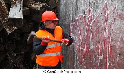 Man with hammer near old wall