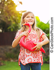 Portrait of cute little girl outside with pink flamingo