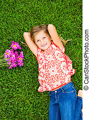 Smiling little girl lying on green grass with flowers