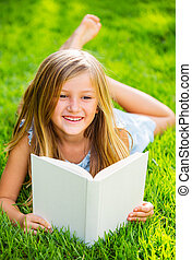 Cute little girl reading book outside on grass, relaxing...