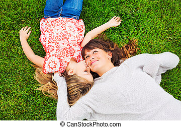 Happy mother and daughter relaxing outside on green grass....