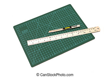 Green cutting mats with iron ruler and cuter isolated on...