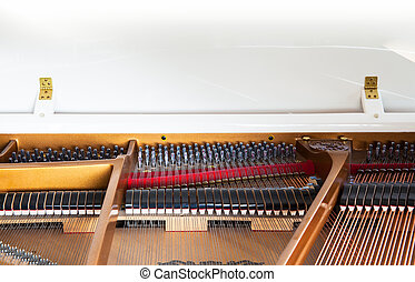 Closeup of white grand piano showing the strings, pegs and...