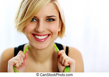Closeup portrait of a young happy woman with measure tape