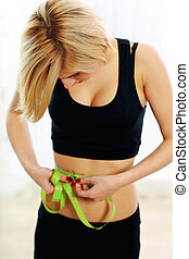 Young fit woman with measure tape