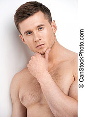 Portrait of handsome thoughtful man with nude chest Standing...