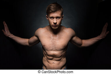 Sexy nude fit male model posing on camera Standing with wide...