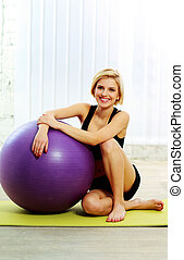 Young happy fit woman sitting on the yoga mat with fitball