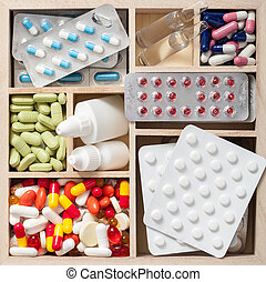 medical pills and ampules in wooden box