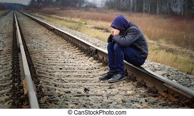 Sorrowful boy on the railway
