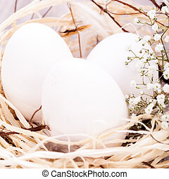 Plain undecorated Easter eggs in a nest - Three plain white...