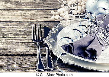 Christmas table setting in silver tone on wooden table