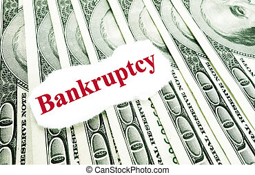 bankruptcy - Bankrupty text on a paper scrap over money...