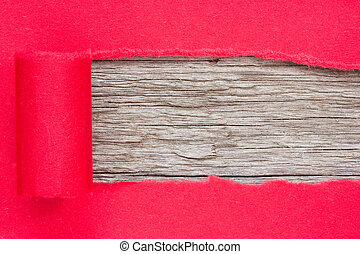 Red paper torn to reveal wooden panel for copy space