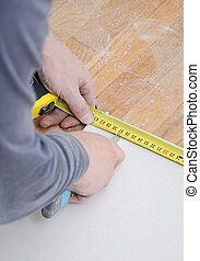 Male hands measuring and cutting gypsum plasterboard