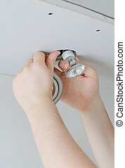 Male hands installing light bulb
