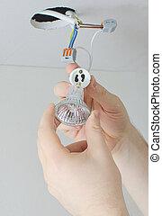 Male hands installing socket for light bulb