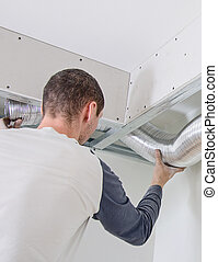 Man setting up ventilation system indoors