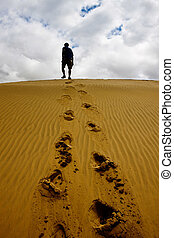 Man walking on a sand dune at Thar desert in Rajasthan,...