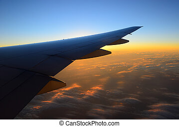 View of jet plane wing with cloud patterns and sunrise