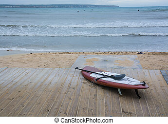 Paddle surfboard on boardwalk, beach, waves and surfers in...