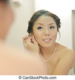 Wedding preparation - Asian bride wearing earrings on her...