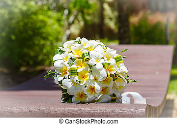 wedding bouquet of frangipani on the bench