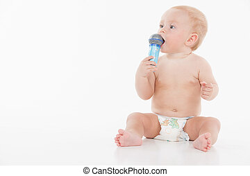 Little funny baby holding microphone and looking at copy...