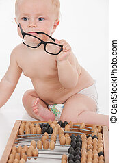 Funny little smart baby holding glasses and sitting by...