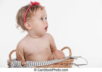 Cut little baby girl in red hoop sitting in basket. Looking...