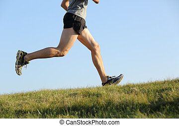 Side view of a jogger legs running on the grass with the...