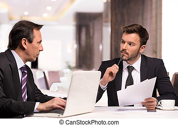 Business partners meeting. Two confident business people in formalwear discussing something while sitting at the restaurant