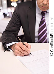 Signing a contract. Close-up of mature man in formalwear signing a document