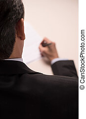 Contract signing. Rear top view of man in formalwear signing a document